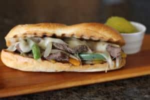 Cheese Steak Sandwich is on a wooden plate