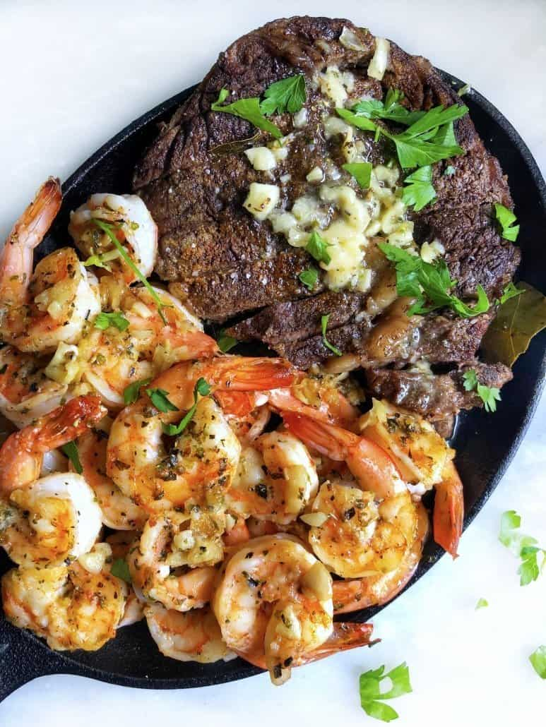 A black pan lays on a counter top. One half of the pan contains shrimp, the other half contains steak.