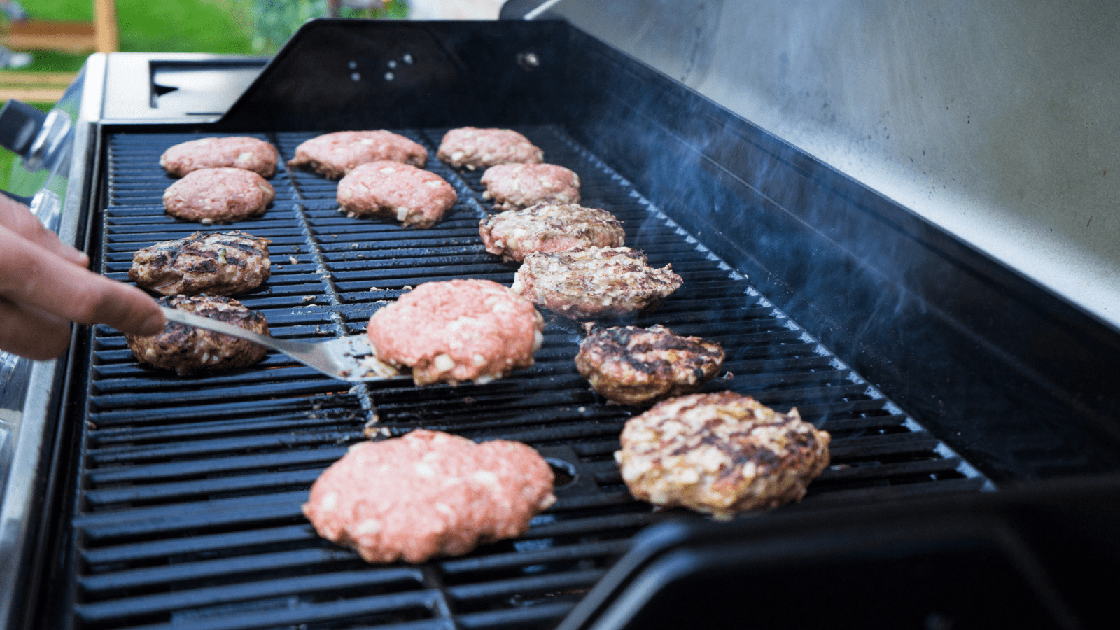 One burger with spatula underneath and a hand ready to flip the burger, multiple burger patties alongside on the same grill.