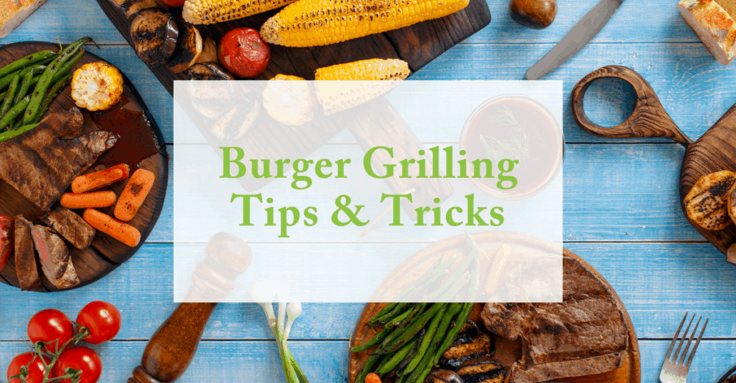 """Blue picnic table with various food items spread across is topped with an opaque white box and text reading """"Burger Grilling Tips & Tricks"""""""