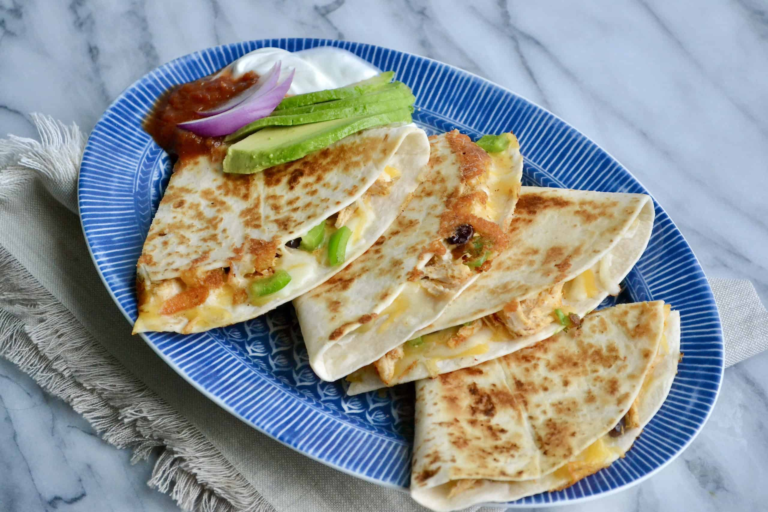 Blue plate holds two chicken quesadillas